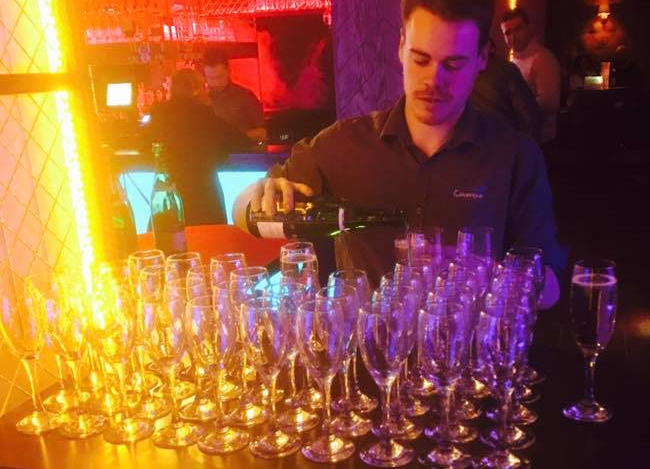 Bar man pouring champagne into flute glasses