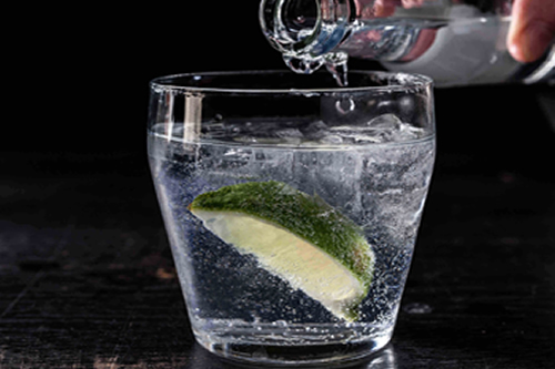 Gin in glass with slice lime and tonic being poured on top