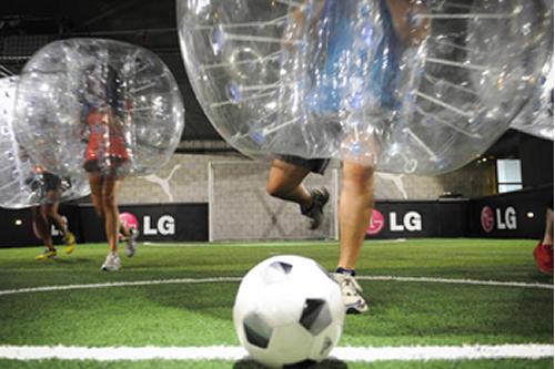 Men in shorts under big bubbles kicking football