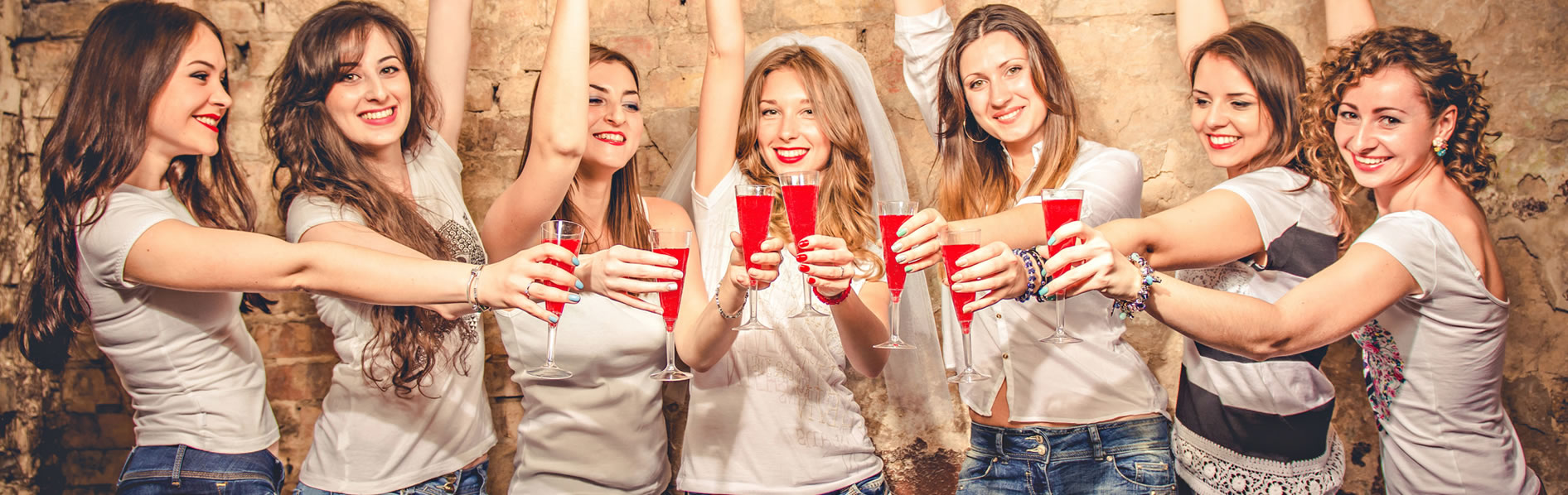 Girls in jeans holding out flutes with red cocktails in